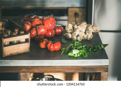 Modern kitchen concrete counter with ingredients for cooking tomato sauce, canned tomatoes or pasta dish with heirloom tomatoes, garlic and basil. Healthy seasonal cooking, slow food