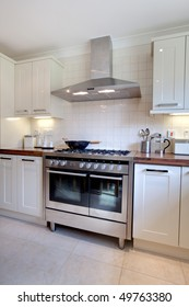 Modern kitchen containing range style stainless steel cooker, matching extractor hood, cupboards and array of utensils and jars standin on the worktop