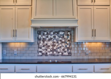 Modern kitchen counter and cabinets with granite counters, white cabinets, cook top, subway tile back splash.