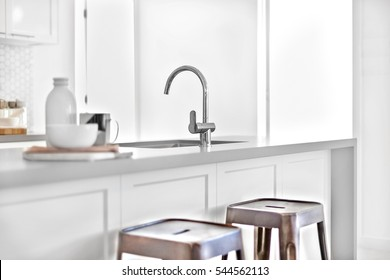 Modern kitchen counter focusing the silver tap and blurred beside a black and plastic chairs near an entrance, ceramic items on wooden table.