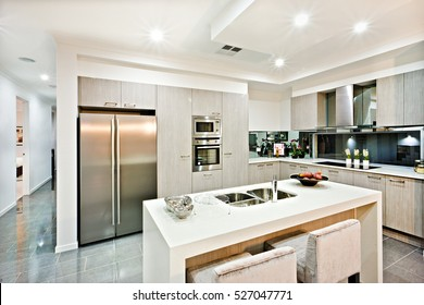 Modern kitchen counter top with a fridge and pantry giving a shiny look the house interior with flashing lights over the tile floor hallway