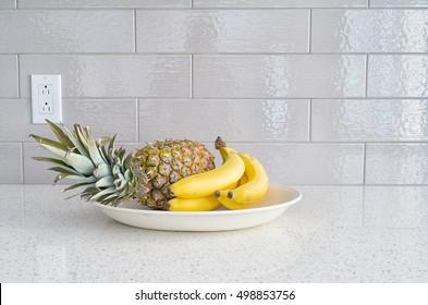 Modern kitchen countertop with fruits dish against gray backsplash