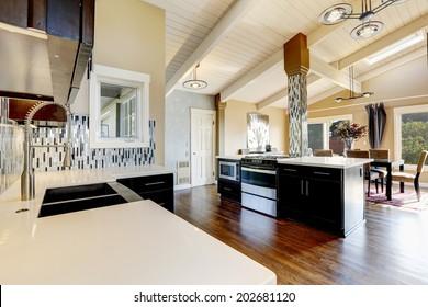 Modern kitchen with dark brown cabinets, steel appliances and kitchen island with bar stools