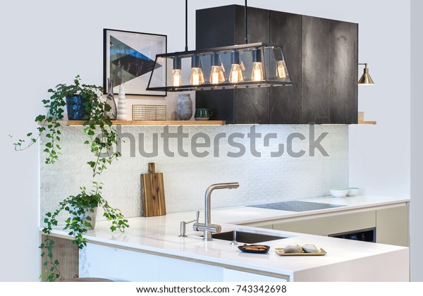 Modern kitchen design in home interior. Facades are painted and made of natural stone. Project management. Loft Light Fixture Lights in Black Metal Frame Shade with Clear Panel Glass. Copper Wire.