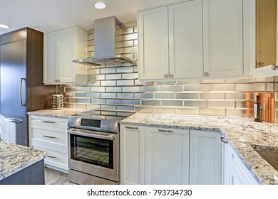 Modern kitchen design with silver backsplash, white shaker cabinets and gray quartzite countertops.