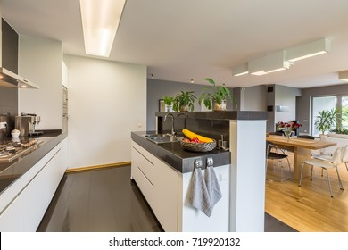 Modern kitchen designed in white and black colors with island