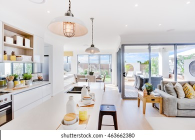 Modern kitchen with a dining and patio area including some utensils on counter top under the hanging lamps closely, the living room with sofa and pillows beside outdoor patio area with sunlight
