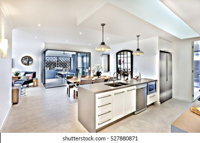 Modern kitchen with a dining room and patio area, there are flashing lamps hanging on the ceiling, over and tap with sink fixed to the counter cupboard. there are door and a hallway to outside patio