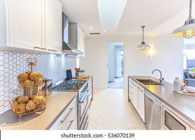 Modern kitchen with fancy items like thread balls on a small rack on the counter which has a stove next to the hallway to the door. There are hanging lamps flashing over the counter with sink and tap