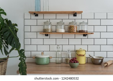 modern kitchen with flower and shelves with products