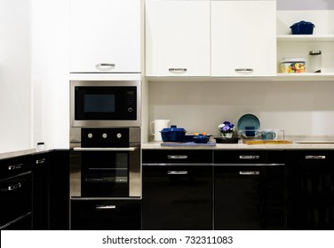 Modern kitchen furniture with contemporary kitchenware like hood, black induction stove and oven in house.