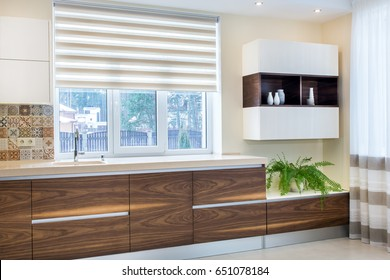 Modern kitchen furniture design in light interior. Wood facades are made from walnut veneer. Without handles. European fittings, appliances, technologies. Cabinets, style, stone surface,pattern tiles.