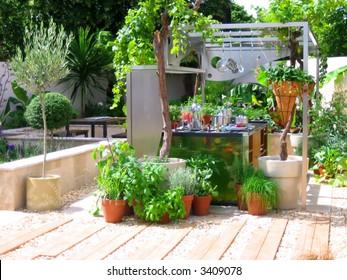 Modern kitchen in the garden with fresh green plants