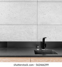 Modern kitchen with grey wall tiles, black worktop, sink and tap