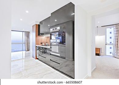 Modern kitchen including a black pantry cupboards beside on the tile floor near to the window see view and the hallway to the house inside through the carpet floor to a glass door which shows outside