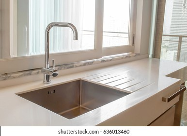 Modern kitchen interior in the city apartment .White marble,quartz counter top kitchen with stainless steel sink and faucet, sliding glass window for service,clean and luxury design.
