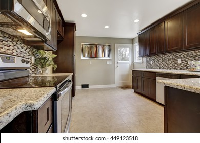 Modern kitchen interior with dark brown storage cabinets with granite counter tops and new tile floor