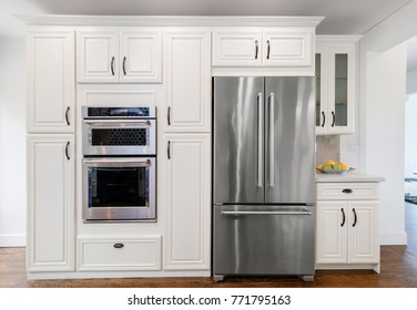 Modern kitchen interior with fitted oven, microwave and refrigerator.