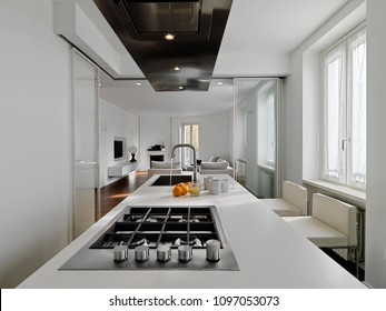 modern kitchen interior in the foreground the cooking hob and the steel hood in the background the living room