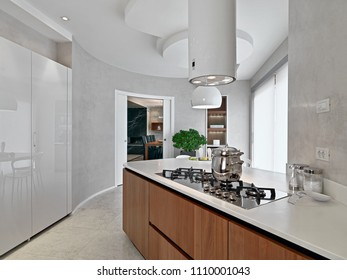 modern kitchen interior in the foreground the cooking hob with a steel pan, overlooking on the living room