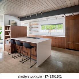 Moderne Küche Räume mit Insel, Sink, Schränke und Beton Boden in stilvollem Haus. Mit Walnussschränken und Schwimmenden Regalen.