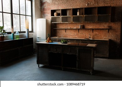 Modern kitchen interior with red brick wall, big window and wooden table