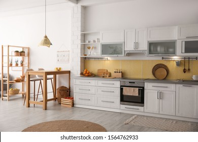 Modern kitchen interior with stylish wooden table - Shutterstock ID 1564762933