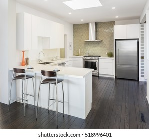 Modern kitchen interior in white with bar stools and wooden floor. Kitchen Design concept