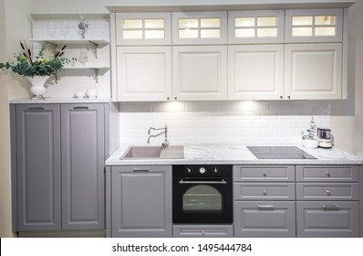 Modern kitchen interior with white brick walls, wooden countertops with a built in sink and a cooker.