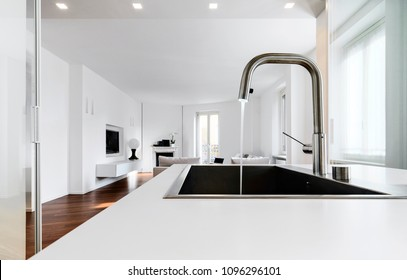 modern kitchen interiors in the foreground the integrated steel sink and the chrome faucet that overlooking on the living area