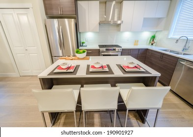 Modern kitchen with island and cabinets in a luxury house set for dinner. Interior design.