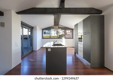 Modern kitchen island in a renovated apartment with a dark colored wooden floor. Everything is empty and there is no one inside