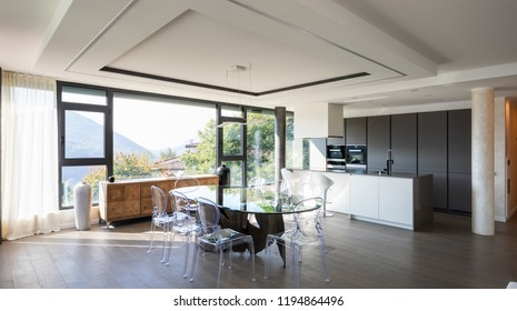 Modern kitchen with island and transparent chairs and table. Nobody inside