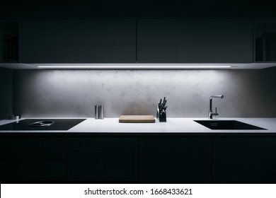 Modern kitchen in minimalist design during night with LED light strip and premium materials such as glass and concrete.Kitchen is complemented by basic kitchen utensils made of high quality materials.