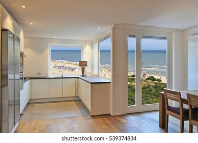 modern kitchen in renovated house with view on beach at summer