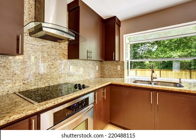 Modern kitchen room with matte brown cabinets, shiny granite tops, steel stove with hood and granite back splash