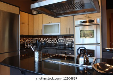 Modern Kitchen with stainless steel appliances and beautiful granite counters and tile back splash.
