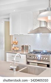Cocina moderna con algunos objetos de lujo en la parte superior de la barra. Hay grifo y fregadero borroso delante de la chimenea y los armarios de la pared blanca