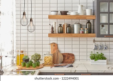 Modern kitchen style white ceramic wall grey kitchen cupboard and wooden shelf decoration. Kitchen objects on the shelf and lamp concept.