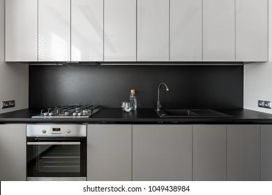 Modern kitchen unit in black and white, black worktop and backsplash