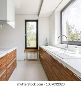 Modern kitchen with white countertop, big window and island