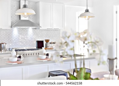Modern kitchen with white decoration and kitchenware including hanging lamps, pantry cupboards and counter are colorful, walls are white color.