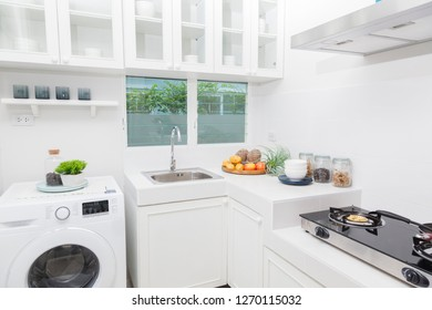 Modern kitchen with white tiles on wall looking onto garden