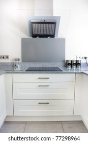 modern kitchen with white units and extrator fan and hob