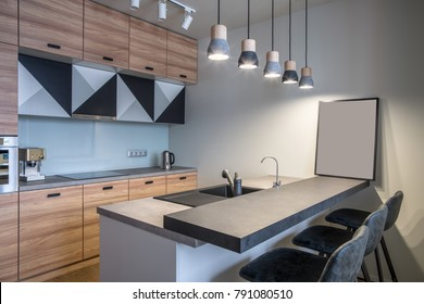 Modern kitchen with white walls and luminous hanging lamps. There is a light kitchen island with a sink and gray tabletops and dark chairs, wooden lockers, oven, stove, chrome kettle, coffee maker.