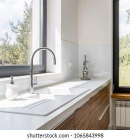 Modern kitchen with white worktop, sink and big window