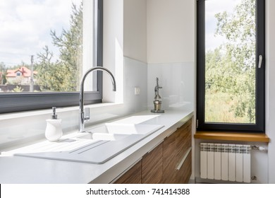 Modern kitchen with white worktop, sink and big window