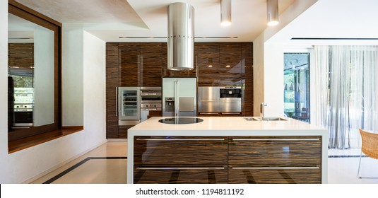 Modern kitchen in wood and marble with island. Nobody inside