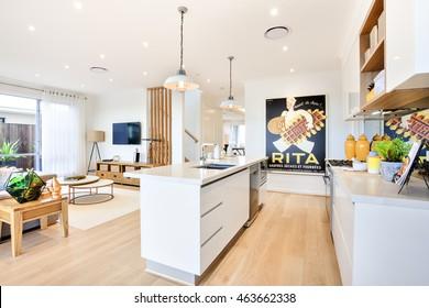 Cocina moderna con suelo de madera y mostrador al lado de armarios llenos de utensilios, salón con muebles y luces colgantes