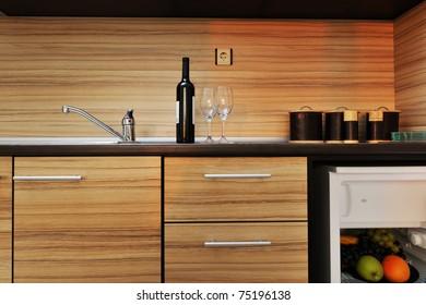 Modern kitchen wooden furniture with sink, blender and fridge